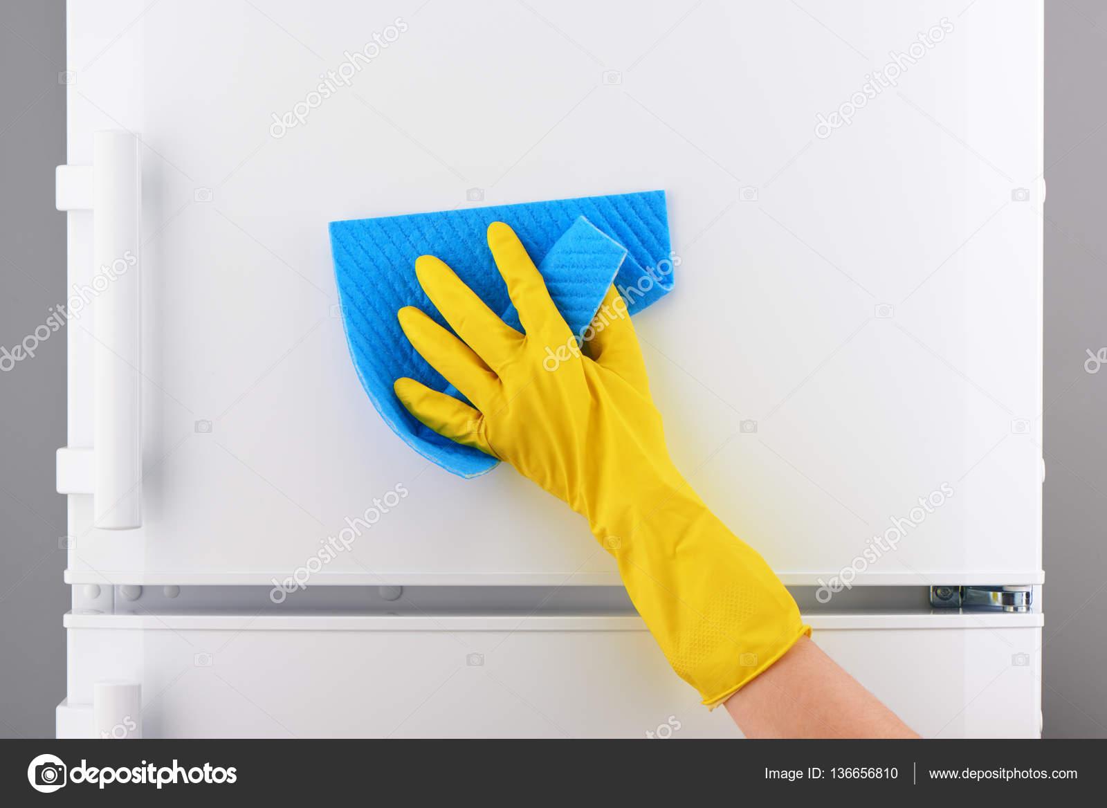 Kühlschrank Reinigen : Hand im gelben handschuh weiß kühlschrank mit blauen lappen reinigen