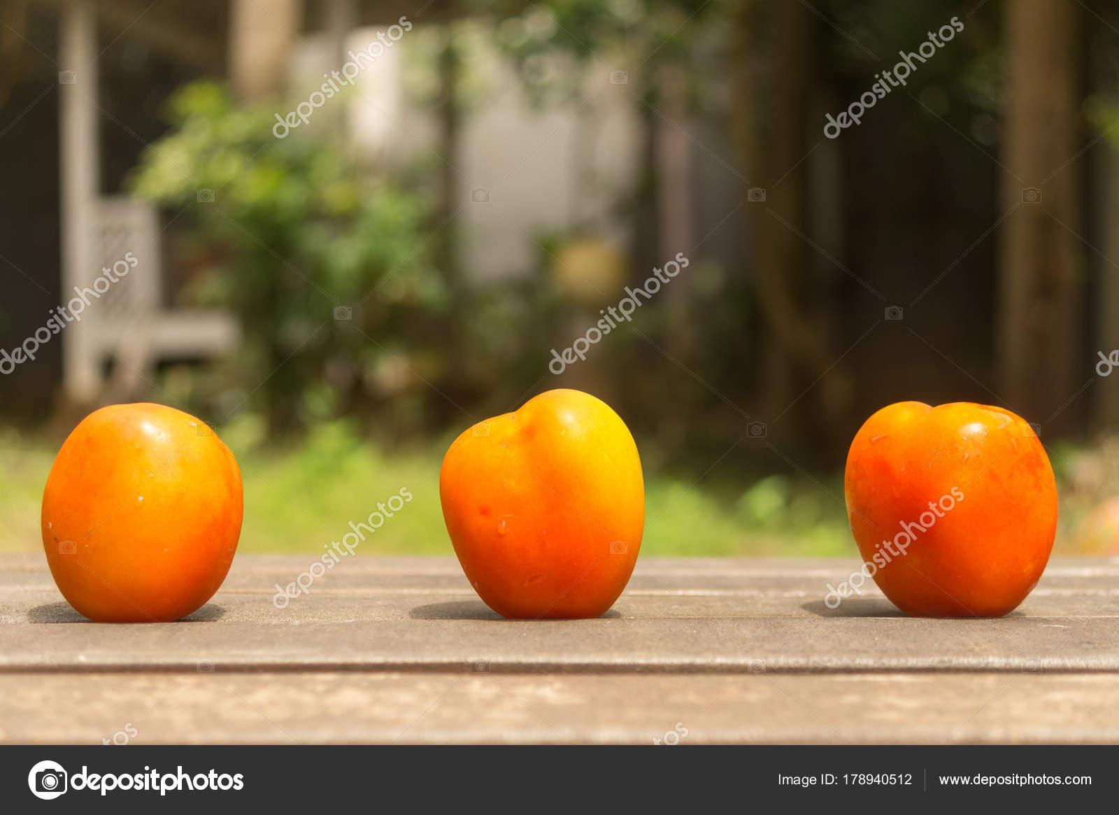 Three Orange Tomato on Wood Ground in Green Garden — Stock Photo ...