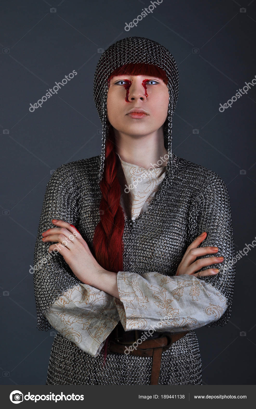 Medieval Girl In Chain Mail With Red Hair Stands On A Gray