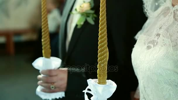 Groom and bride hold thick white candles in their hands during the ceremony
