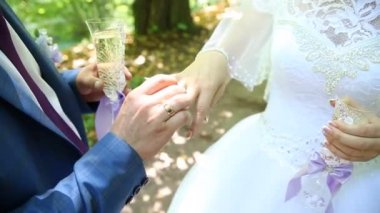 On a wedding day bride puts a golden ring on a groom finger Close