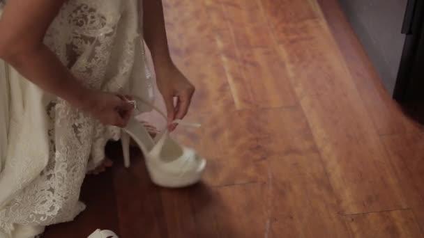 Die Braut trägt weiße Brautschuhe mit ihren Händen
