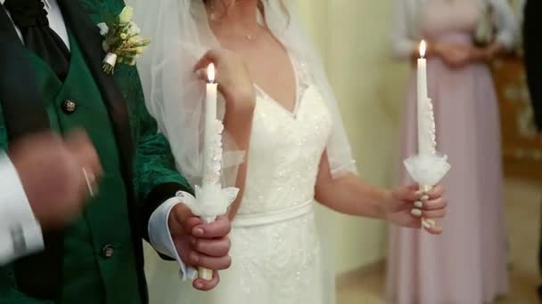 The church, the bride and groom hold candles on the wedding