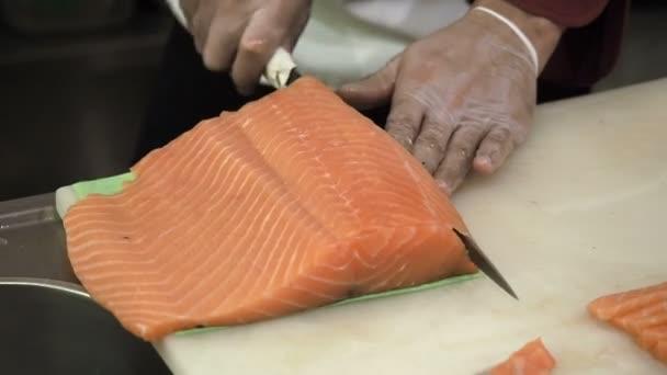 Folyamat a döntéshozatalban és a vágás lazac sushi tekercs. Főzni felvágják a halat késsel vékony szeletekre.