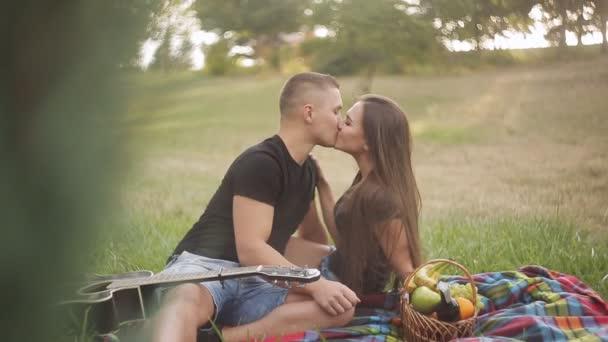 Junge schöne Paar gekleidet, lässig mit Picknick im Park, Trauben Essen und Wein trinken