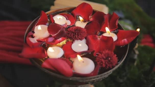 Gyertyák égnek lassan rózsaszirommal vázában. romantikus dekor