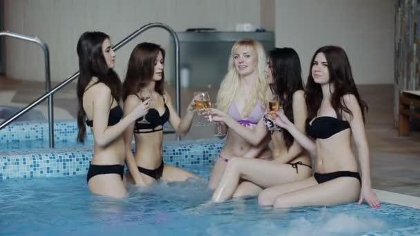 five beautiful girls in bikini drinking champagne at the pool