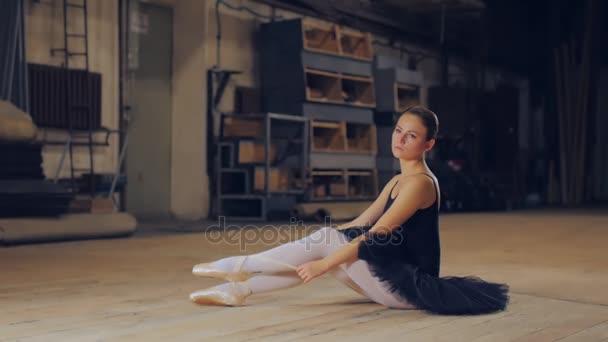 schöne junge Ballerina bindet Spitzenschuhe auf dem Hintergrund der Holzwand