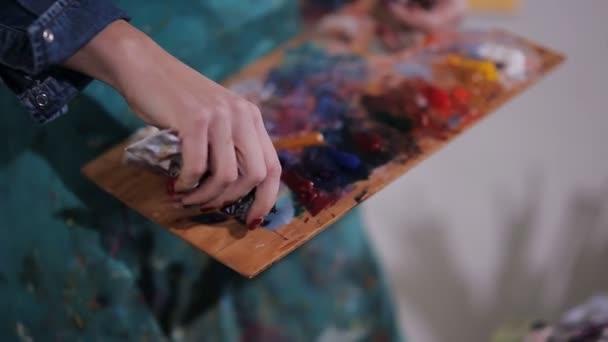umělec vytlačuje trubice barvy na paletě. detail