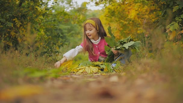 cheerful girl sitting on the footpath and throwing autumn leaves. Slow-motion