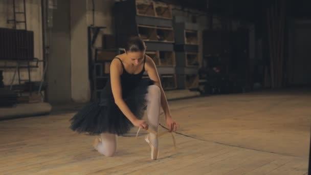 Ballerina bindet Spitzenballettschuhe auf der Bühne.