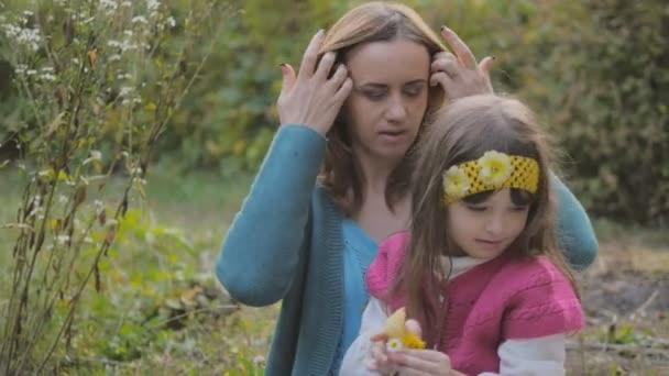 Mutter und ihre kleine Tochter amüsieren sich im Freien. schöne Familie-Mutter und ihr Kind Mädchen umarmen und küssen sich im Park zusammen.