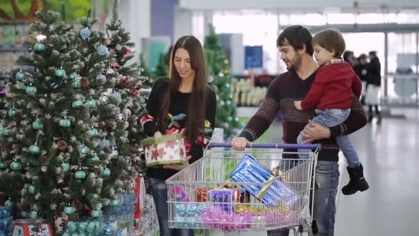 Bella famiglia è lo shopping per Natale al supermercato. Mamma prende le sfere di Natale del figlio e ragazzo sorridente.