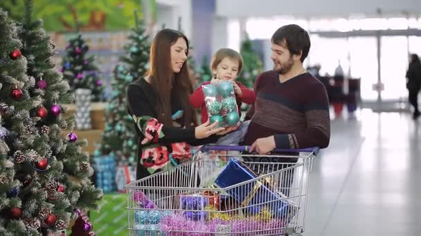 Christmas shopping in a supermarket. A young family is shopping in a supermarket for Christmas. Mother, father and son are choosing toys for the Christmas tree.