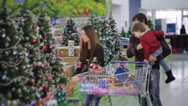 Shopping in un supermercato di Natale. Una giovane famiglia è lo shopping in un supermercato per Natale. Madre, padre e figlio scelgono giocattoli per lalbero di Natale.