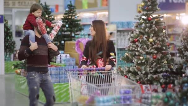 Bella famiglia che cammina lungo il corridoio con un supermercato shopping carrelli e opta per i giocattoli di Natale e Natale regali.
