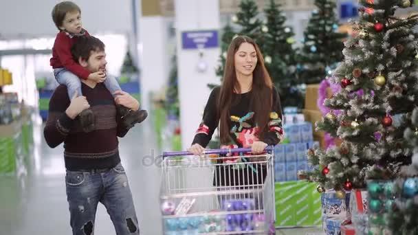 Bella famiglia che cammina lungo il corridoio con un supermercato shopping carrelli e opta per i giocattoli di Natale e Natale regali. Ragazzino che si siede nello shopping carrello e considerare lacquisto di.