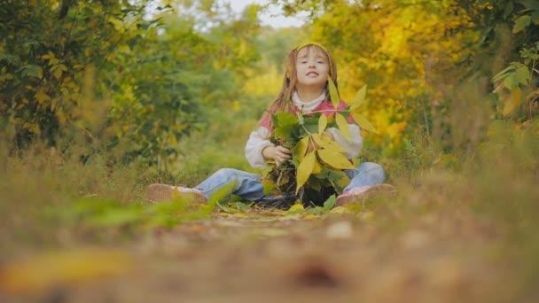 krásná holčička s dlouhými vlasy hodí žluté a zelené listy sedící na stezce. Dítě se směje. Podzim v městském parku