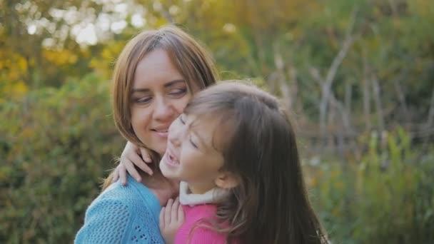 Holčička s dlouhými vlasy se směje a obejme mámu za krk. šťastný matka a dcera směje a víru. pomalý pohyb