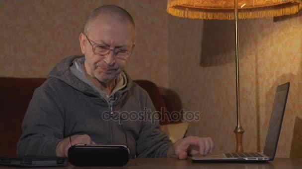 Opa sitzt am Schreibtisch und arbeitet an einem Laptop. Ist die Eingabe