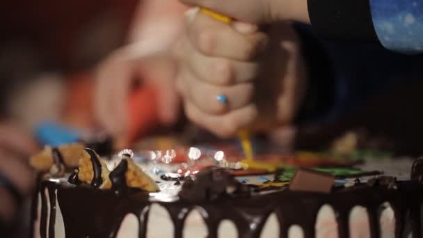 gyermek kezét közelről a egy zsák péksütemény présel a krémet a tortán