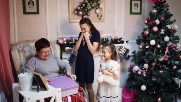 Weihnachtsgeschenk Weihnachten.Großmutter Packt Geschenk Enkelin Hat Oma Weihnachtsgeschenk Das Geräumige Wohnzimmer Ist Mit Weihnachten Spielzeug Kerzen Und Weihnachtsbaum Dekoriert