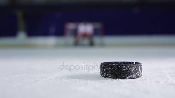 Hokejista držící demonstraci volného hodu do protivníků brány hokejový puk a odjel do rozjížděk v čisté odpůrci
