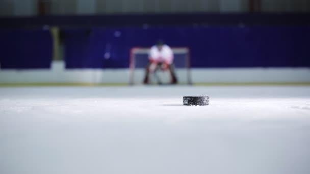 Hokejista držící demonstraci volného hodu do protivníků brány hokejový puk a odjel do rozjížděk v čisté odpůrci.