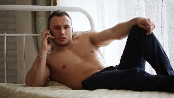 muž ležel v posteli a mluví po telefonu s dívkou