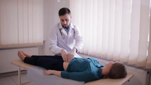 Lékař dělá prohmatání břicha pacienta. Dívka leží na gauči v kanceláři lékaři.