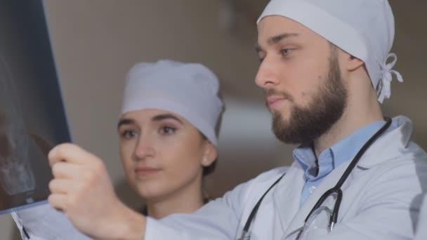 Tři mladí lékaři při pohledu na rentgen páteře. Zpomalený pohyb