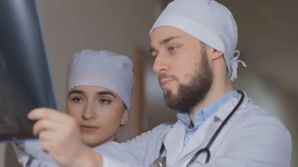 Lékař zkoumá x-ray obrázek a stážistka vysvětluje co onemocnění pacienta