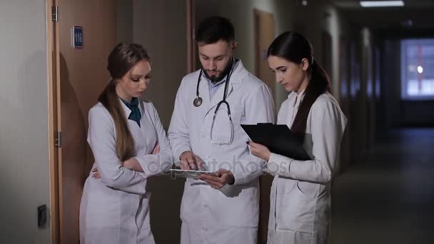 Doctor with two girls interns parses the diagnosis of the patient.