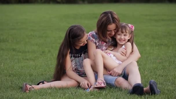 Happy mother with two daughters in a park on the grass