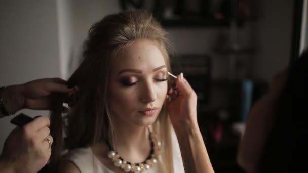 Profesionální kadeřník dělá účes pro dlouhé vlasy modelu. Maskérka je pro atraktivní dívka krásná, makeupclose-up, kadeřník dělá účes