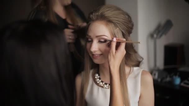 Profesionální kadeřník dělá účes pro dlouhé vlasy modelu. Detail, kadeřník dělá účes. Maskérka je pro atraktivní dívky nádherné líčení