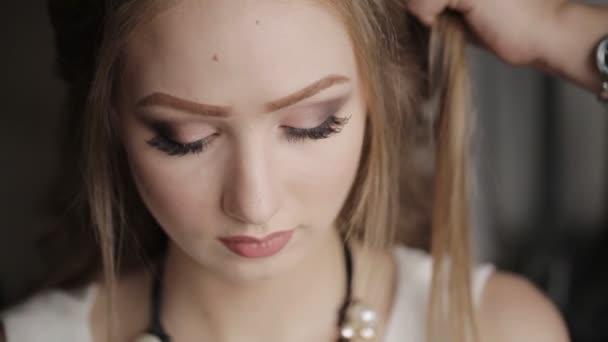 Profesionální kadeřník dělá účes pro dlouhé vlasy modelu. Maskérka je pro krásné atraktivní dívka Make-up Close-up, kadeřník dělá účes