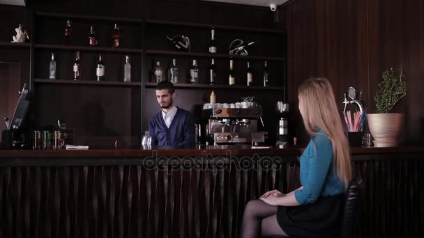 girl sitting at the bar and waiting for the bartender to prepare a cocktail
