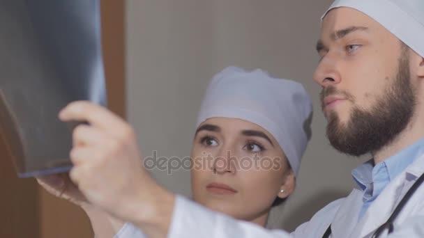 Arzt untersucht ein Kollege von Röntgenbild und erklärt, dass es notwendig, einen Patienten zu ernennen