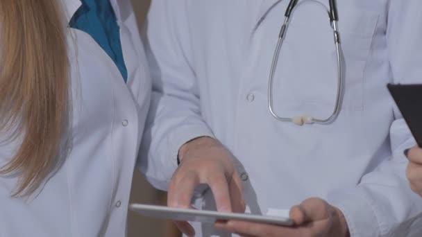 Nahaufnahme der Hände des Arztes unter Berücksichtigung des Kardiogramms des Patienten auf dem Tablet.