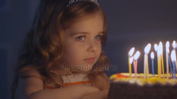 Holčička se dívá na svíčky na slavnostní dort a dělá přání v pomalém pohybu