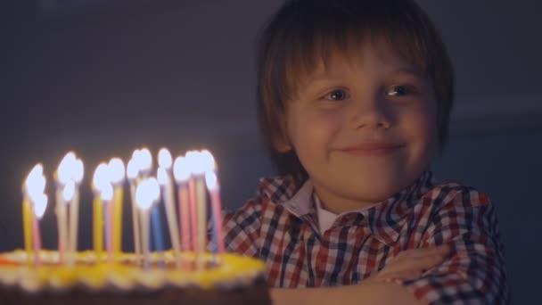 Usměvavý chlapec dělá přání než sfouknete svíčky na narozeninový dort