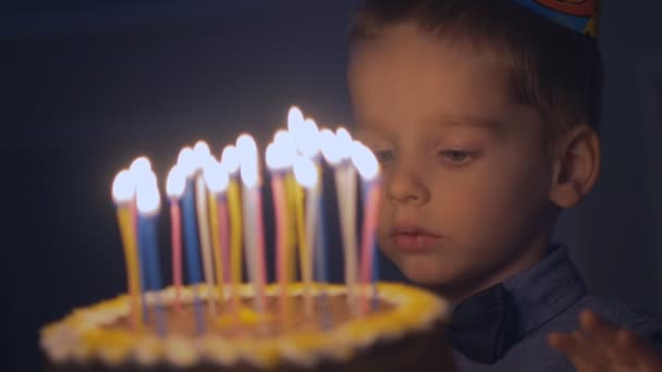 Thoughtful boy tries finger cream with cake with candles. boy blows out candles on birthday cake in Slow motion