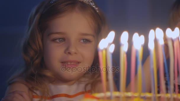 Piccola bella ragazza sta soffiando nove candele sul compleanno torta al rallentatore. Una bambina felice esamina le candele su una torta festiva e lei fa desiderare