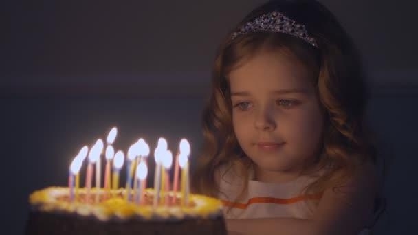Egy kislány gyertyák egy ünnepi torta néz ki, és teszi egy kívánsága, lassítva