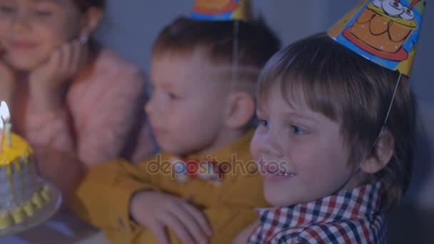 malé děti sedět u stolu, červené s dortem a vyhodit v barevné party dmychadla na narozeninovou oslavu.