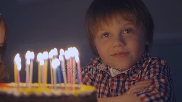A mosolygó fiú tesz kívánja, mielőtt Ön elfújni a gyertyákat, egy születésnapi torta, ban lassú mozgás
