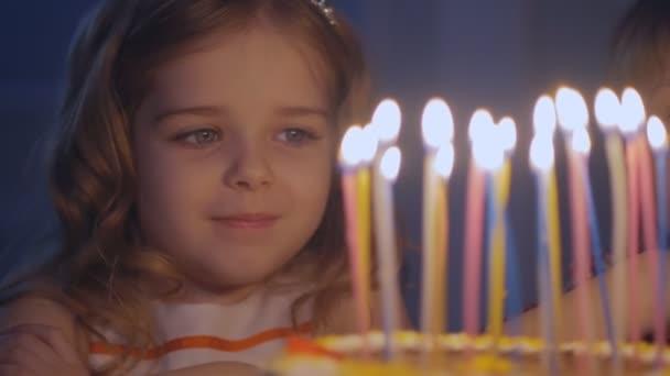Šťastná holčička se dívá na svíčky na slavnostní dort a činí ji přát v pomalém pohybu