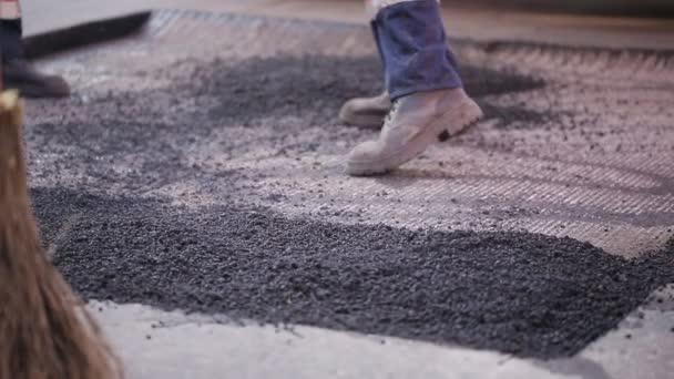 Dělníci asfalt poškozenou část silnice