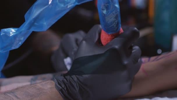Profesionální tatér provede tetování na ruce mladé holky tetování umělce, aby tetování ve studiu, zblízka